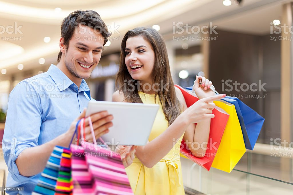 Happy couple using digital tablet during the shopping stock photo