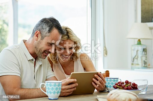 Happy couple using digital tablet at table in house