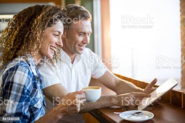 Happy couple using digital tablet while having coffee in a caf picture id641344348?b=1&k=6&m=641344348&s=612x612&h=kyrqedzl txmeq xx yxfa885b51yrszdrsazucrxt4=