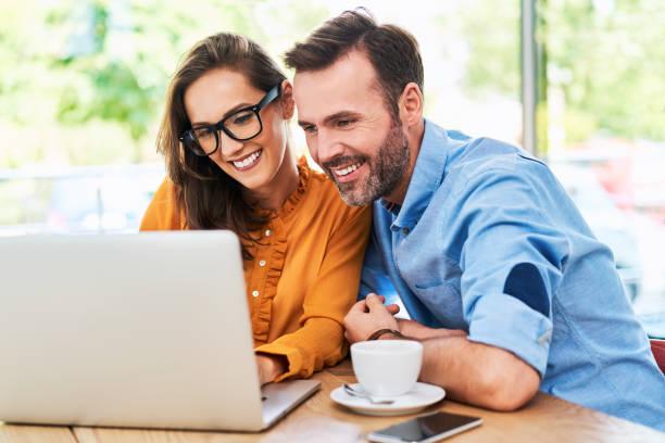 Glückliches Paar mit Laptop im Café genießen Zeit zusammen – Foto