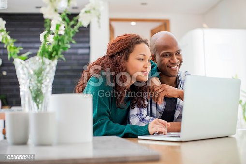 Happy couple using laptop at table in living room. Smiling man and woman are enjoying at home. They are spending leisure time.