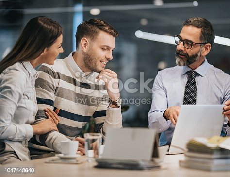 istock Happy couple using laptop with their insurance agent in the office. 1047448640