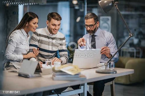 istock Happy couple using laptop with their insurance agent in the office. 1131851341