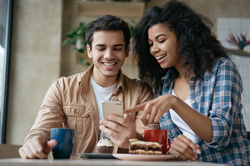 Young happy couple using mobile phone application for online shopping. Emotional friends communication, laughing, looking at digital screen, sitting together in cafe