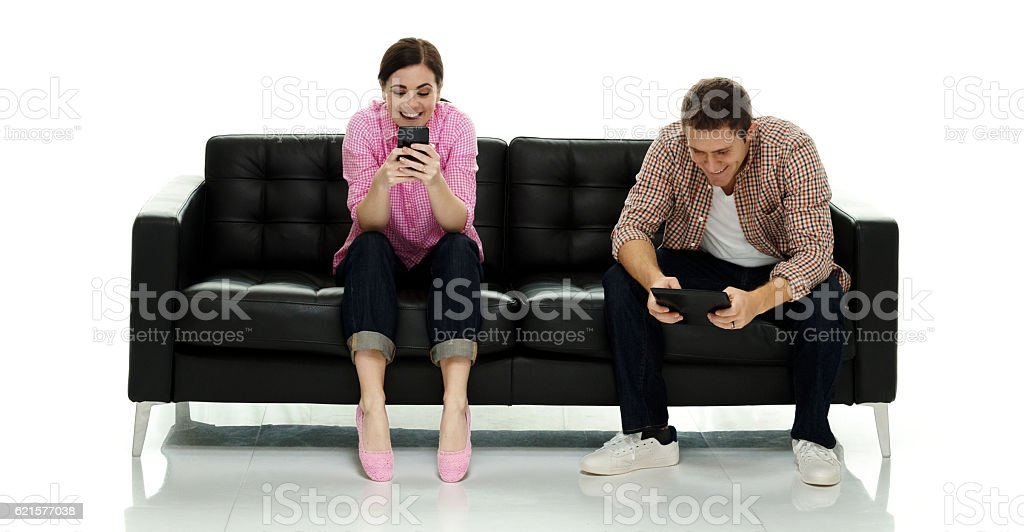 couple heureux à l'aide de téléphone et tablette photo libre de droits