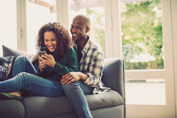 casal feliz usando telefone inteligente no sofá em casa - 30 39 anos - fotografias e filmes do acervo