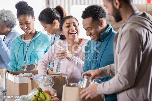 istock Happy couple volunteer in community food bank 961524688