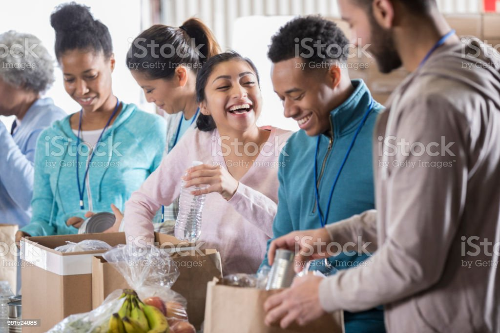 Happy couple volunteer in community food bank stock photo
