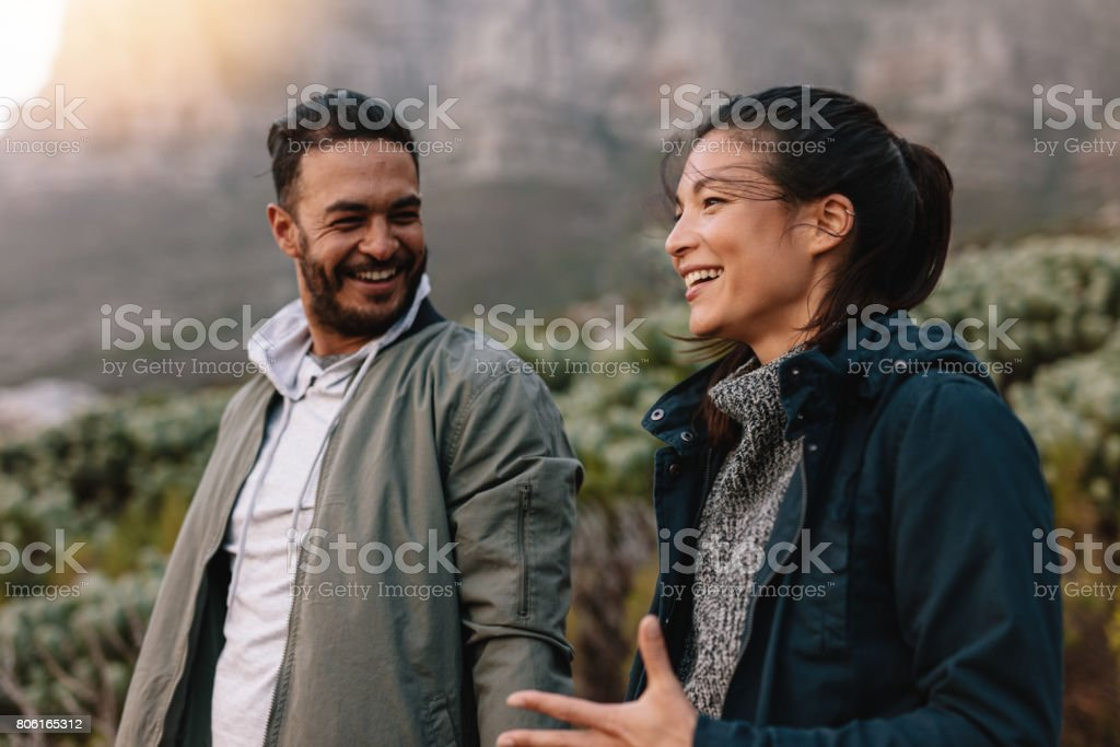 Happy couple walking and talking in the countryside royalty-free stock photo
