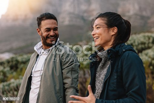 istock Happy couple walking and talking in the countryside 806165312