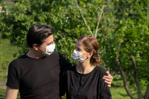 Happy couple walking at public park with protective masks during Covid-19 stock photo