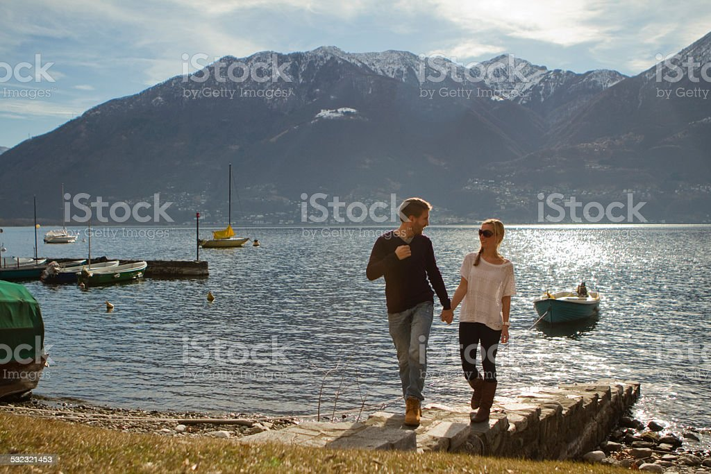 Happy couple walking by the lake stock photo