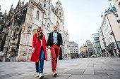 Romantic couple is walking on the Vienna street, holding hands. Autumn season.