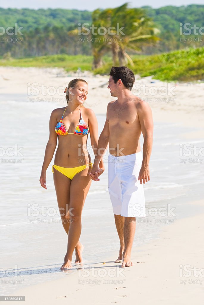 Happy couple walking in a tropical beach royalty-free stock photo