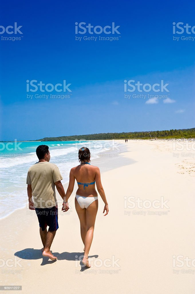 Happy couple walking in a tropical beach stock photo