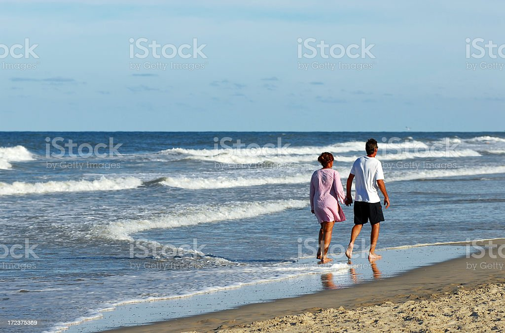 Happy couple walking on a beach royalty-free stock photo