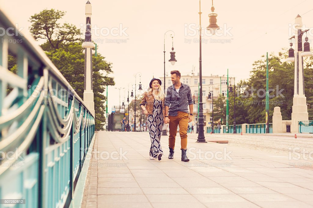 Happy couple walking on the sidewalk, holding hands royalty-free stock photo