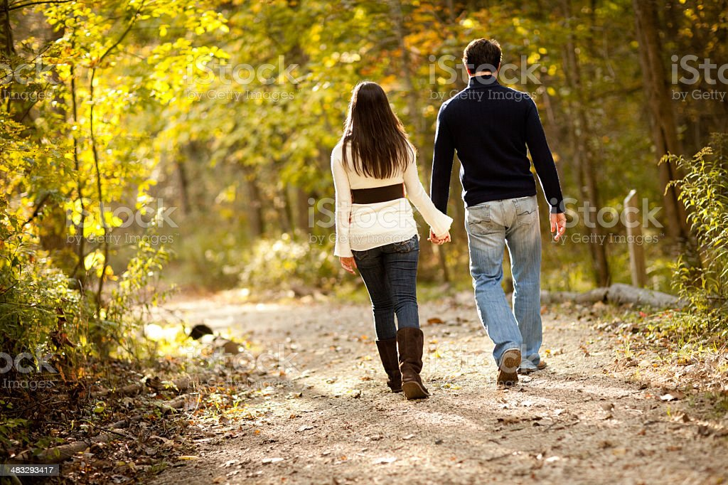 Happy Couple Walking Together in Autumn Woods royalty-free stock photo