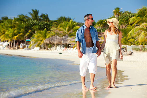 Happy Couple Walks Beach A happy couple walks hand-in-hand along tropical Caribbean beach while looking lovingly in each others eyes. Roatan, Honduras roatan stock pictures, royalty-free photos & images