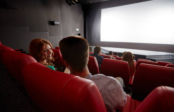 happy couple watching movie and talking in theater stock photo