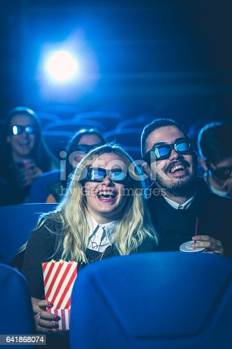 187095683 istock photo Happy couple watching movie together 641868074