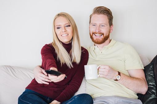 973962076 istock photo Happy couple watching TV in living room 969156106