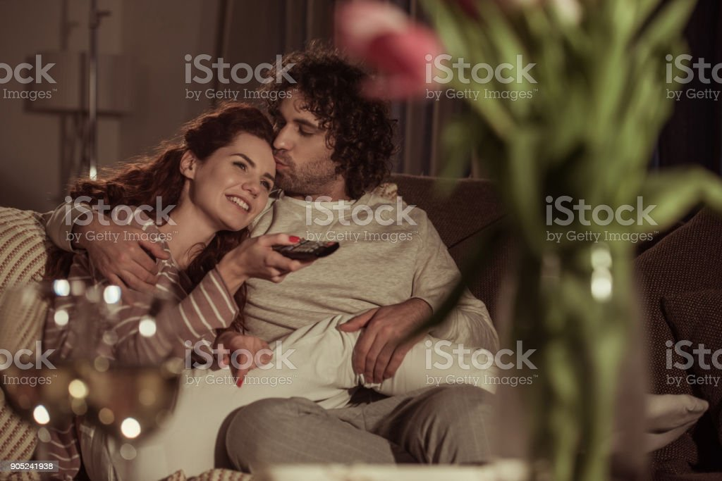 happy couple watching tv on sofa in evening stock photo