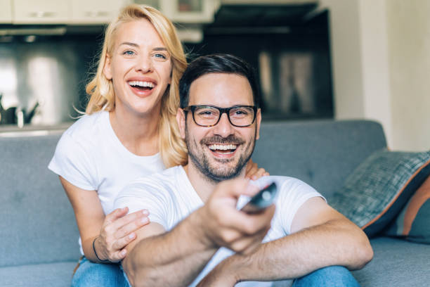 Happy couple watching tv Portrait of beautiful young couple happy together watching tv at home cable tv stock pictures, royalty-free photos & images