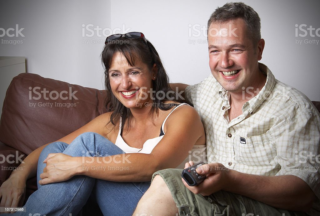 Happy couple watching TV royalty-free stock photo