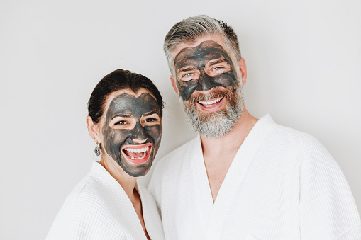 istock Happy couple wearing a charcoal mask 965879876