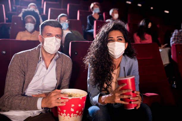 Happy couple wearing face masks at the cinema stock photo
