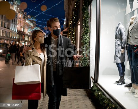 Happy couple wearing facemasks while shopping for their Christmas presents during the COVID-19 pandemic in London