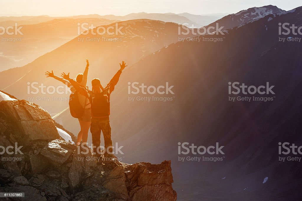 Happy couple winner mountain top concept stock photo