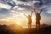 Happy couple stands in winner pose with rised arms on background of sunrise mountains and sea. Success concept
