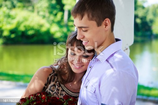510491454istockphoto Happy couple with a bouquet of red roses 161760322