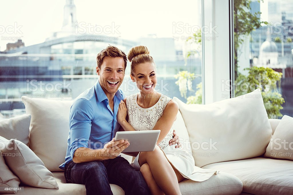 Happy couple with a digital tablet Young couple sitting on sofa in an apartment, holding a digital tablet and laughing at the camera. 25-29 Years Stock Photo