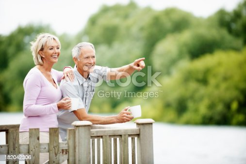 istock Happy couple with a man pointing at something interesting 182042306
