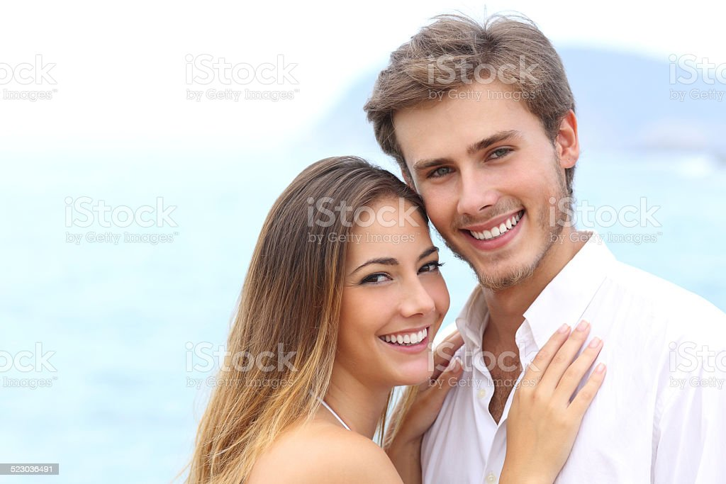 Happy couple with a white smile looking at camera stock photo