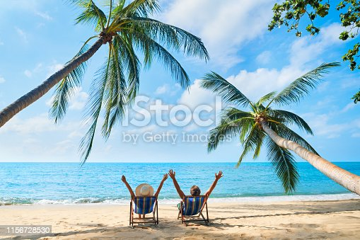 istock Happy couple with arms up relax on the beach enjoy beautiful sea on the tropical island 1156728530