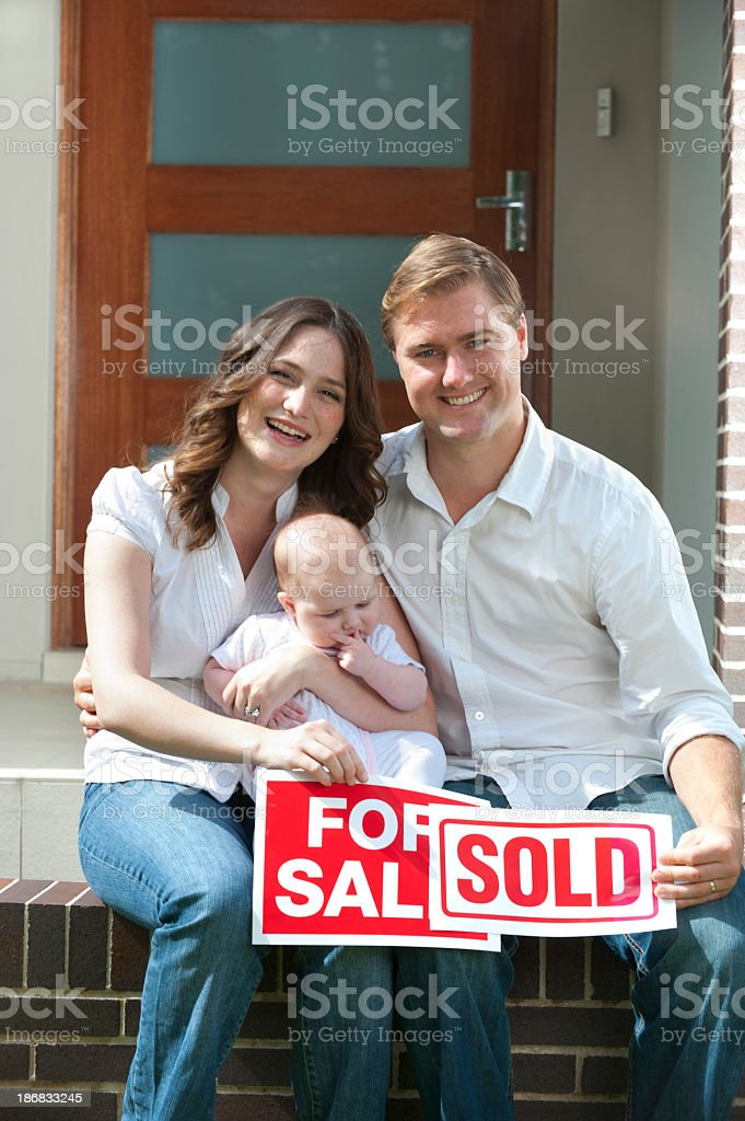Happy couple with baby holding for sale and sold signs royalty-free stock photo