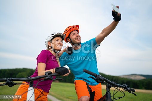 couple man and woman sitting on their  bikes dirt road rural surrounding meadow recreation outdoor workout closer wideangle looking into smartphone taking selfie