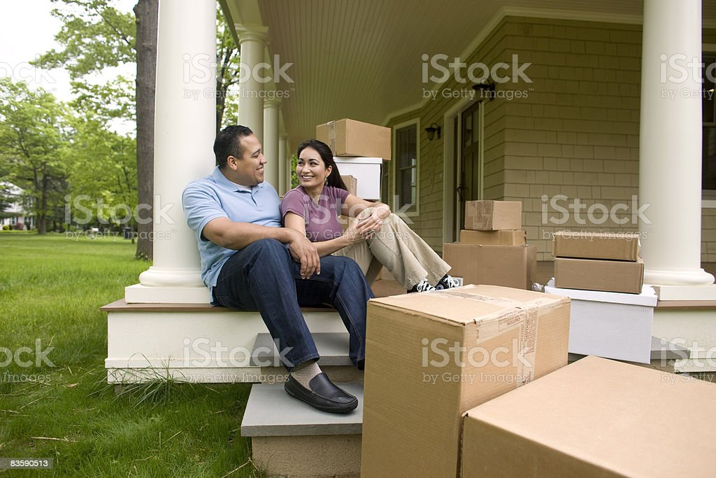 Happy couple with boxes, talking on porch stock photo