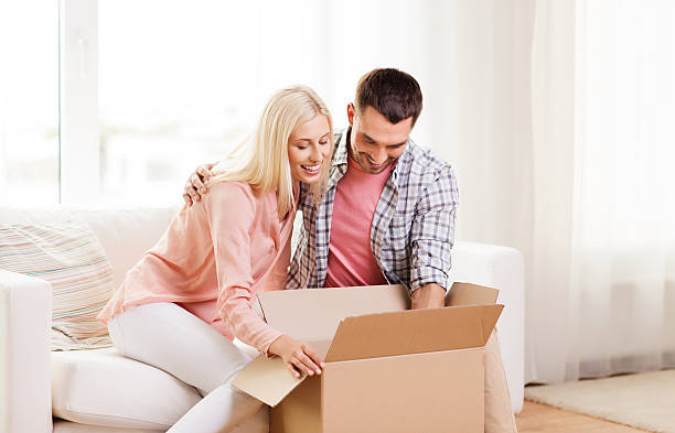 happy couple with cardboard box or parcel at home stock photo