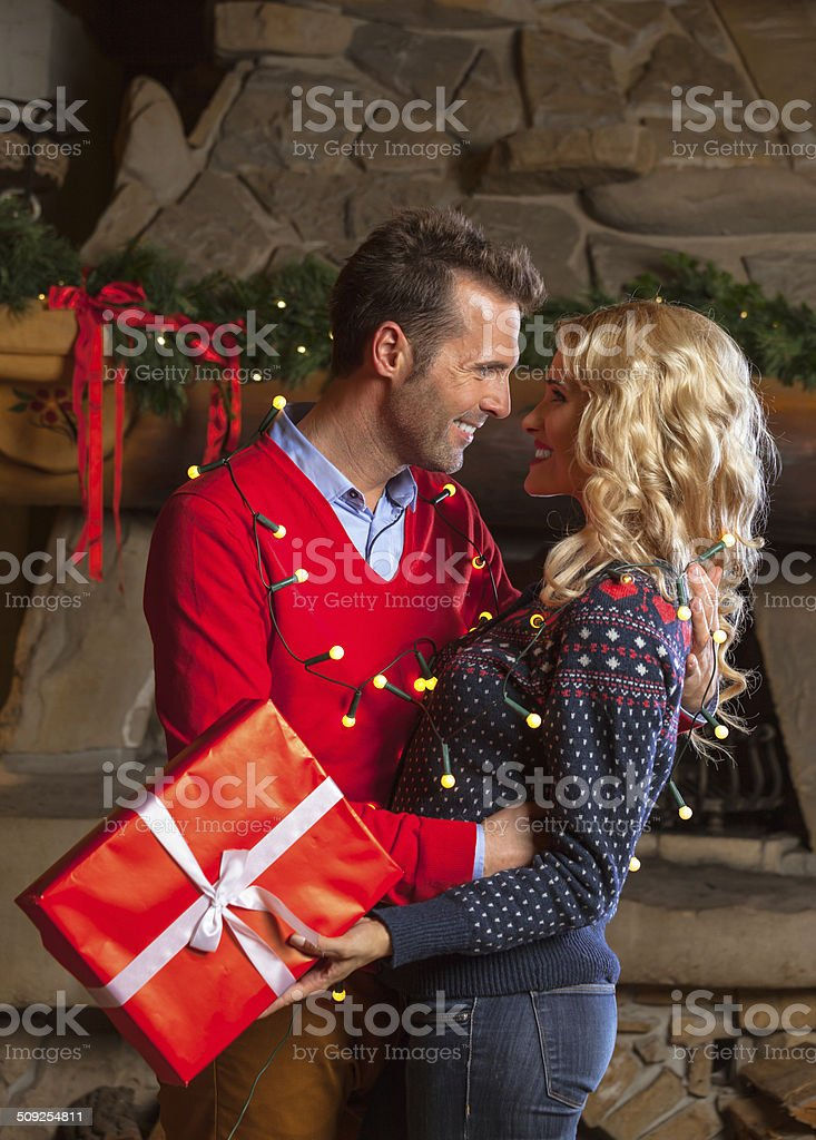 Happy couple with christmas gift Happy couple hugging and exchanging christmas gifts with fireplace in the background. Adult Stock Photo
