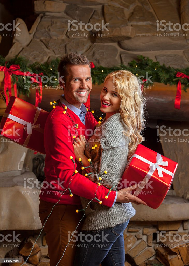 Happy couple with christmas gift Happy couple hugging and exchanging christmas gifts at home with fireplace in the background. Adult Stock Photo