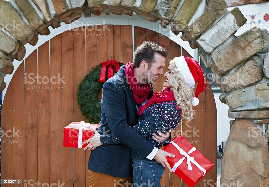 Happy couple with christmas gifts Outdoor portrait of beautiful couple hugging and holding christmas gifts. Adult Stock Photo
