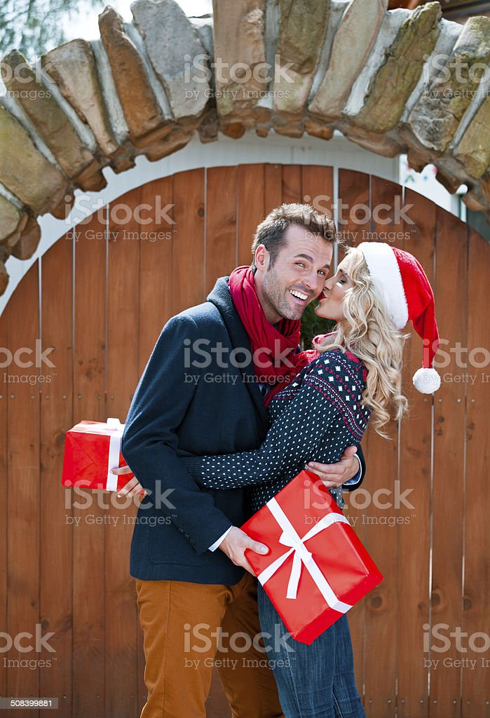 Happy couple with christmas gifts Outdoor portrait of beautiful couple hugging and holding christmas gifts. Woman kissing her partner. Adult Stock Photo