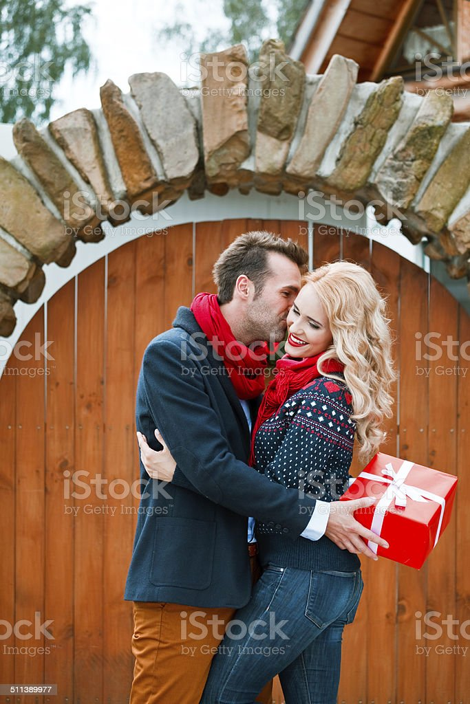 Happy couple with christmas gifts Outdoor portrait of beautiful couple hugging, man holding christmas gift in hands. Adult Stock Photo