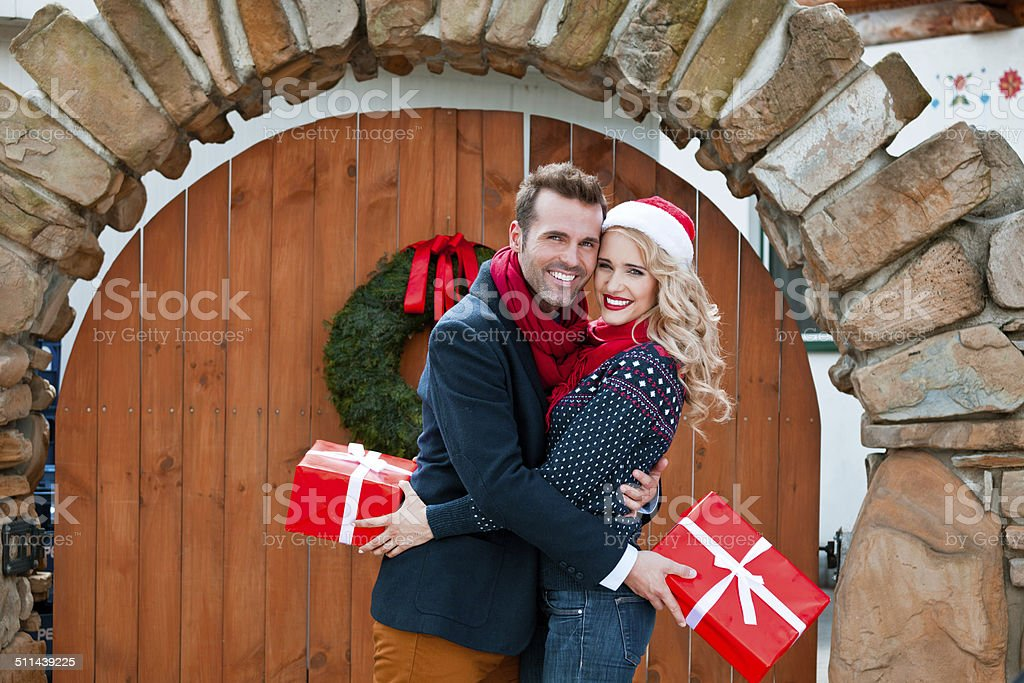 Happy couple with christmas gifts Outdoor portrait of beautiful couple hugging and holding christmas gifts, smiling at camera. Adult Stock Photo