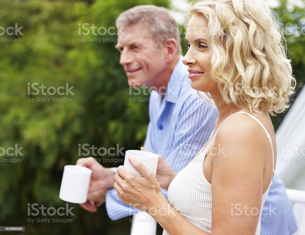 Happy couple with coffee cups looking away royalty-free stock photo